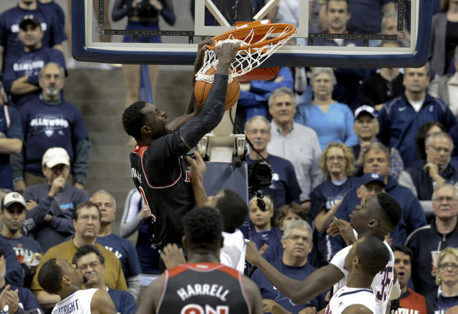 Louisville's Mangok Mathiang dunks the ball during the first half of an NCAA college basketball game against Connecticut, Saturday, Jan. 18, 2014, in Storrs, Conn. (AP Photo/Jessica Hill)