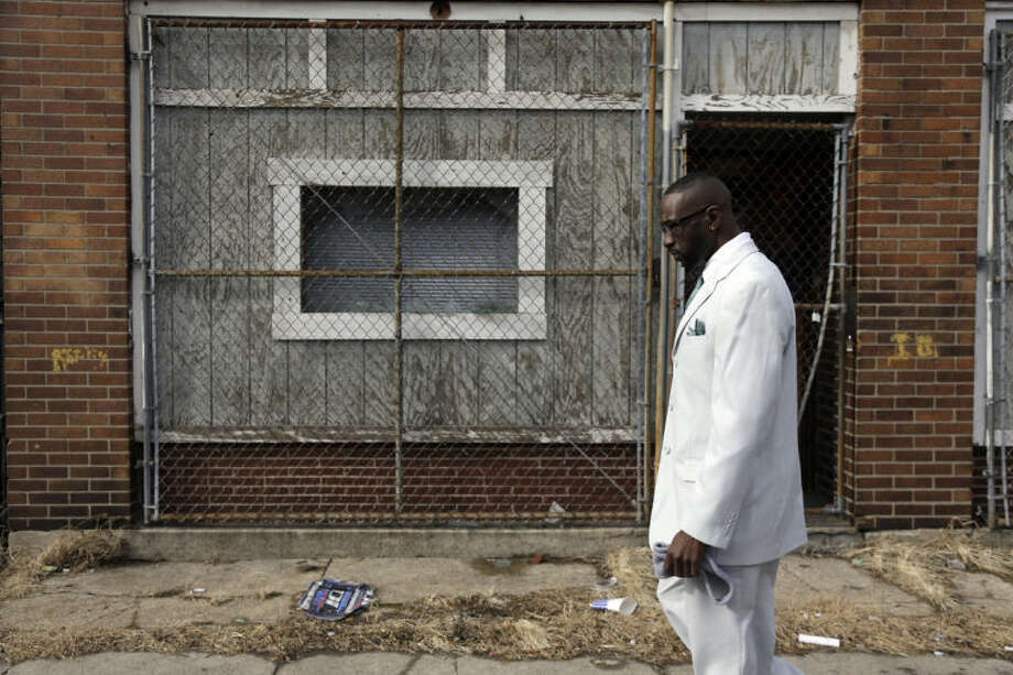 In this Thursday, Jan. 16, 2014 photo, Melvin White, founder of the Beloved Streets of America project, walks past a boarded up building during a tour of Dr. Martin Luther King Jr. Drive in St. Louis. The nonprofit is working to revitalize a downtrodden six-mile stretch of the drive named for the slain civil rights leader, marked by vacant lots, crumbling buildings and a preponderance of liquor stores, pawn shops and check-cashing businesses. Project leaders hope revitalize MLK's streets that have fallen into disrepair in cities around the country. (AP Photo/Jeff Roberson)