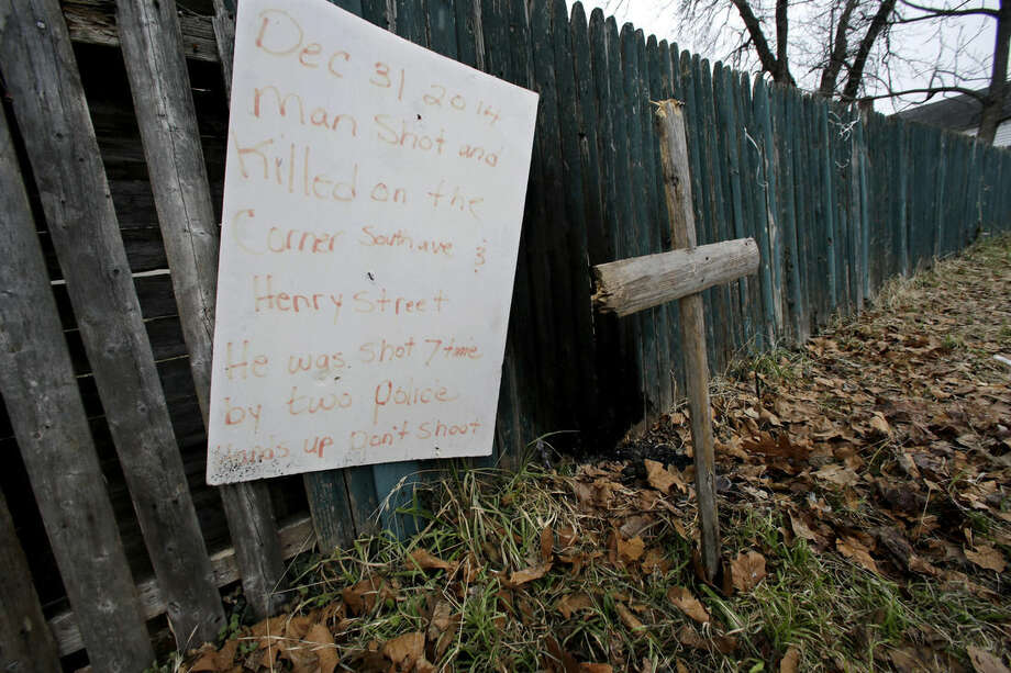 A sign and cross are displayed on Wednesday, Jan. 21, 2015, in Bridgeton, N.J., near where a Dec. 30, 2014 police stop resulted in the fatal shooting of Jerame Reid. (AP Photo/Mel Evans)