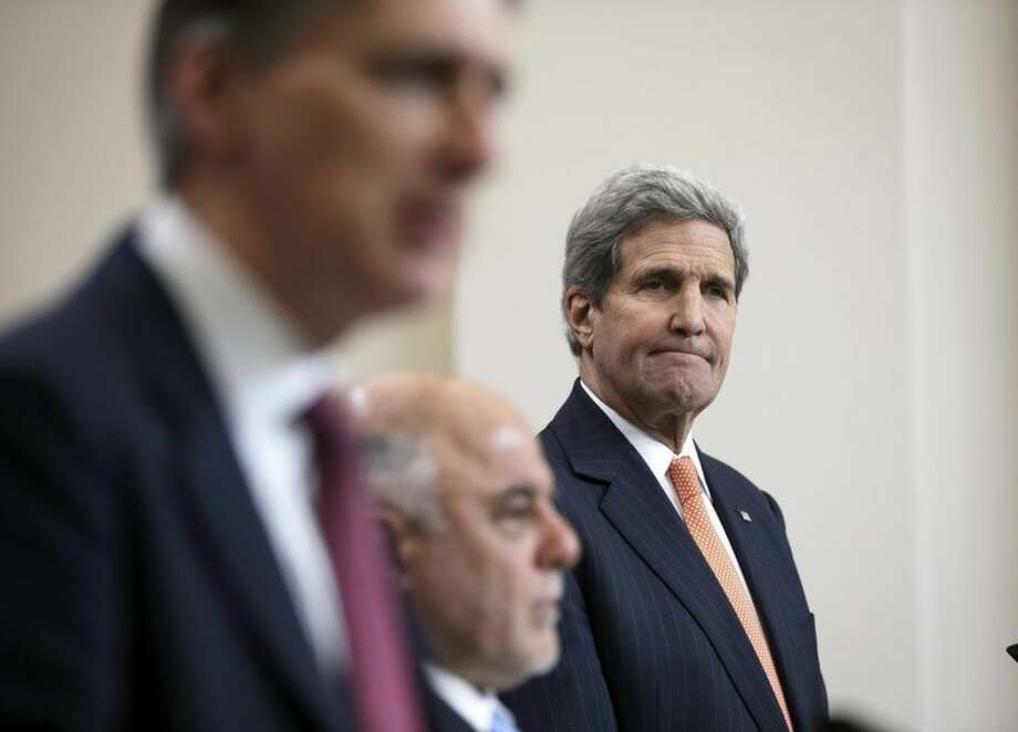 Iraq's Prime Minister Haider al-Abadi, center, and U.S. Secretary of State John Kerry, right, listen as Britain's Foreign Secretary Philip Hammond speaks during a press conference at the Foreign and Commonwealth Office in London, Thursday, Jan. 22, 2015. U.S. Secretary of State John Kerry says Iraq and its international partners have made significant gains in the fight against Islamic State militants, killing thousands of the group's fighters and 50 percent of its leadership. (AP Photo/Peter Nicholls, Pool)