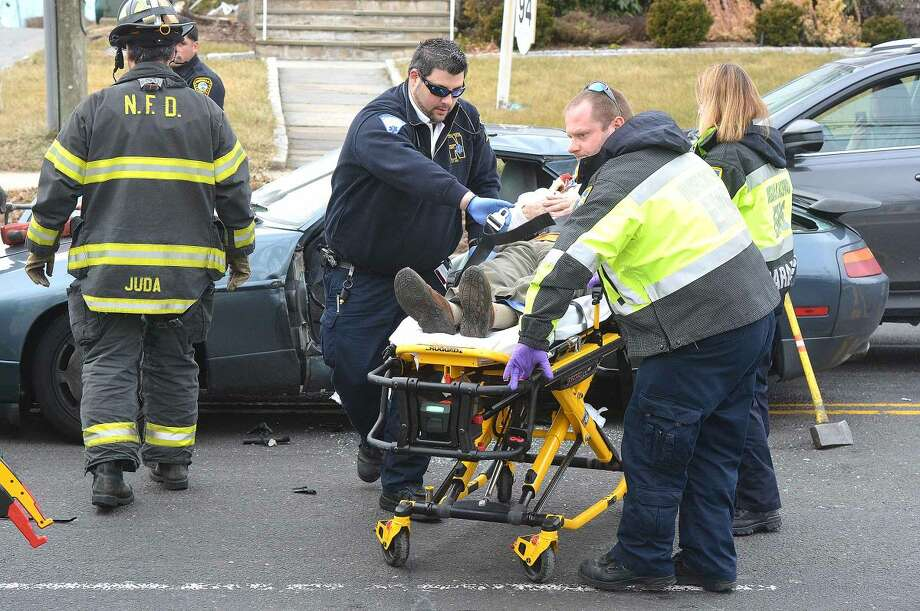 Hour Photo/Alex von Kleydorff The driver of a Porsche 928 is removed from his vehicle after a multi car accident on East Ave in Norwalk Wednesday