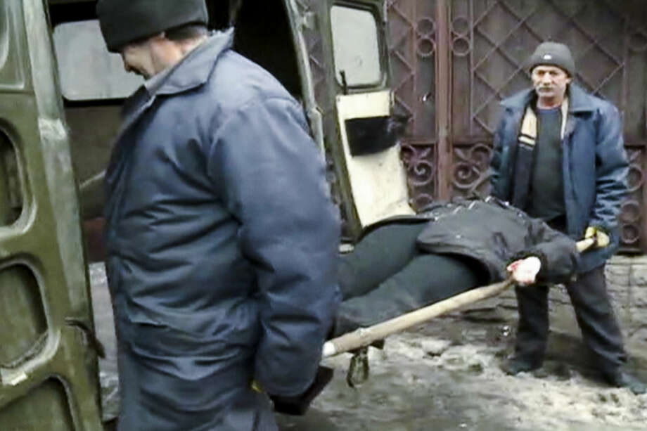 In this image made from the Russian RU-RTR television channel, a victim of a mortal shell which destroyed a trolley bus is carried away in Donetsk, eastern Ukraine, Thursday, Jan. 22, 2015. It's unclear which side was responsible for the attack, which killed passengers instantly and blew out the windows of a nearby building. A separatist defense official blames Ukrainian government forces. (AP Photo/ RU-RTR Russian Television Channel) TV OUT