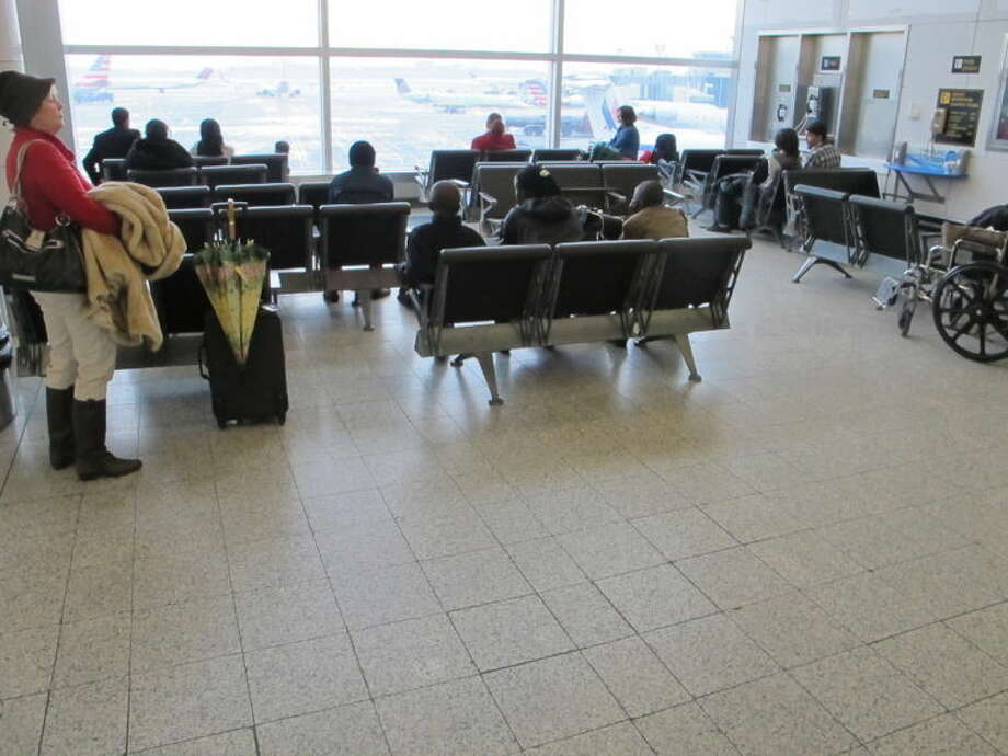 In this Jan. 10, 2014 photo, passengers sit in one of the waiting areas at New York's LaGuardia Airport. Often referred to as dark, dingy, cramped and sad by travelers, LaGuardia Airport is slated from a major renovation project. When completed there will be an entirely new Central Terminal Building, retail shops, restaurants and other amenities, plus new parking garages and other support facilities. (AP Photo/Frank Eltman)