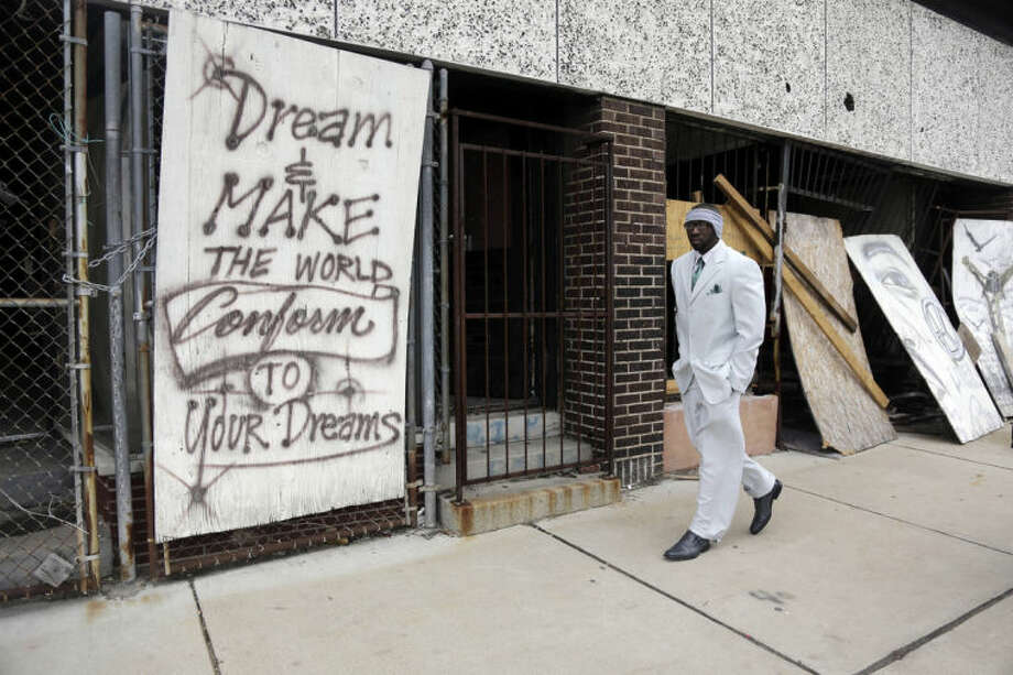In this Thursday, Jan. 16, 2014 photo, Melvin White, founder of the Beloved Streets of America project, walks past a boarded up building during a tour of Dr. Martin Luther King Jr. Drive in St. Louis. The nonprofit is working to revitalize a downtrodden six-mile stretch of the drive named for the slain civil rights leader, marked by vacant lots, crumbling buildings and a preponderance of liquor stores, pawn shops and check-cashing businesses. Project leaders hope revitalize MLK's streets that have fallen into disrepair in cities around the country. (AP Photo/Jeff Roberson) (AP Photo/Jeff Roberson)