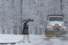 A woman walks under the cover of an umbrella as she walks past a snow plow in Atkinson, N.H., Friday, Feb. 5, 2016. What started off as rain Friday morning quickly turned to sticky, heavy snow. Many school districts in the region closed for the day, including in some in Massachusetts, New Hampshire and Rhode Island. (AP Photo/Charles Krupa)