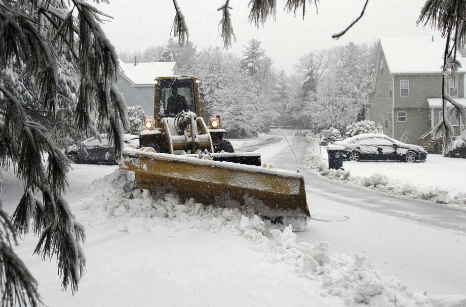 A plow driver clears snow from a road Friday, Feb. 5, 2016, in Marlborough, Mass. What started off as rain Friday morning quickly turned to sticky, heavy snow. Many school districts in the region closed for the day, including in some in Massachusetts, New Hampshire and Rhode Island. (AP Photo/Bill Sikes)