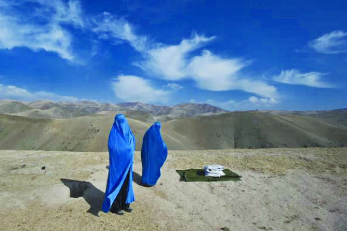 """Contributed photo Westport native and Pulitzer Prize-winning photojournalist Lynsey Addario will open an exhibition at Westport Arts Center, titled """"On The Wire: Veiled Rebellion,"""" on Jan. 24. The photographer provides the following description for the photo above, which will appear in the show:I saw two women on the side of the mountain, in burkas and without a man. In Afghanistan you seldom see an unaccompanied woman. Noor Nisa, about 18, was pregnant; her water had just broken. Her husband, whose first wife had died during childbirth, was determined to get Noor Nisa to the hospital in Faizabad, a four-hour drive from their village in Badakhshan Province. His borrowed car broke down, so he went to find another vehicle. I ended up taking Noor Nisa, her mother, and her husband to the hospital, where she delivered a baby girl. My interpreter, who is a doctor, and I were on a mission to photograph maternal health and mortality issues, only to find the entire story waiting for us along a dusty Afghan road."""