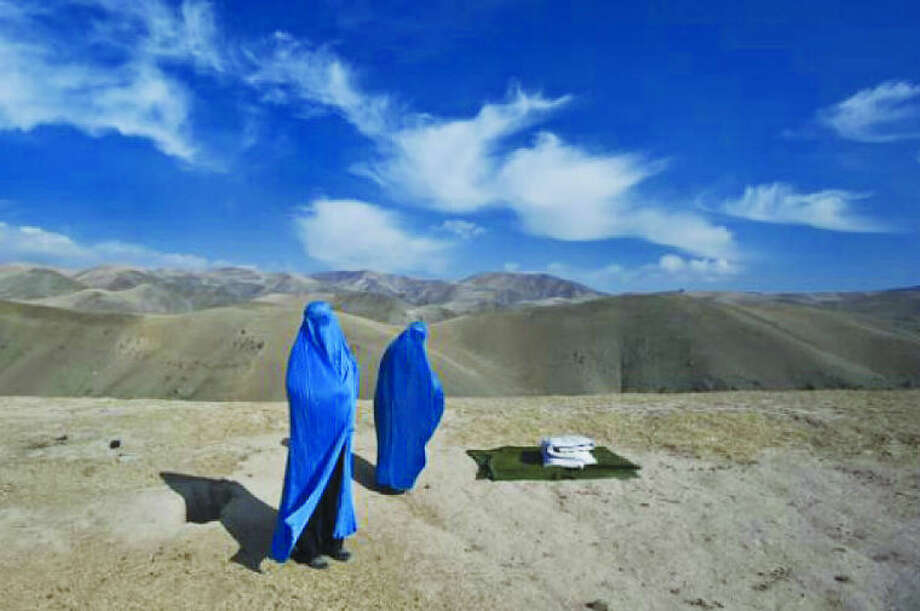 "Contributed photo Westport native and Pulitzer Prize-winning photojournalist Lynsey Addario will open an exhibition at Westport Arts Center, titled ""On The Wire: Veiled Rebellion,"" on Jan. 24. The photographer provides the following description for the photo above, which will appear in the show: I saw two women on the side of the mountain, in burkas and without a man. In Afghanistan you seldom see an unaccompanied woman. Noor Nisa, about 18, was pregnant; her water had just broken. Her husband, whose first wife had died during childbirth, was determined to get Noor Nisa to the hospital in Faizabad, a four-hour drive from their village in Badakhshan Province. His borrowed car broke down, so he went to find another vehicle. I ended up taking Noor Nisa, her mother, and her husband to the hospital, where she delivered a baby girl. My interpreter, who is a doctor, and I were on a mission to photograph maternal health and mortality issues, only to find the entire story waiting for us along a dusty Afghan road."
