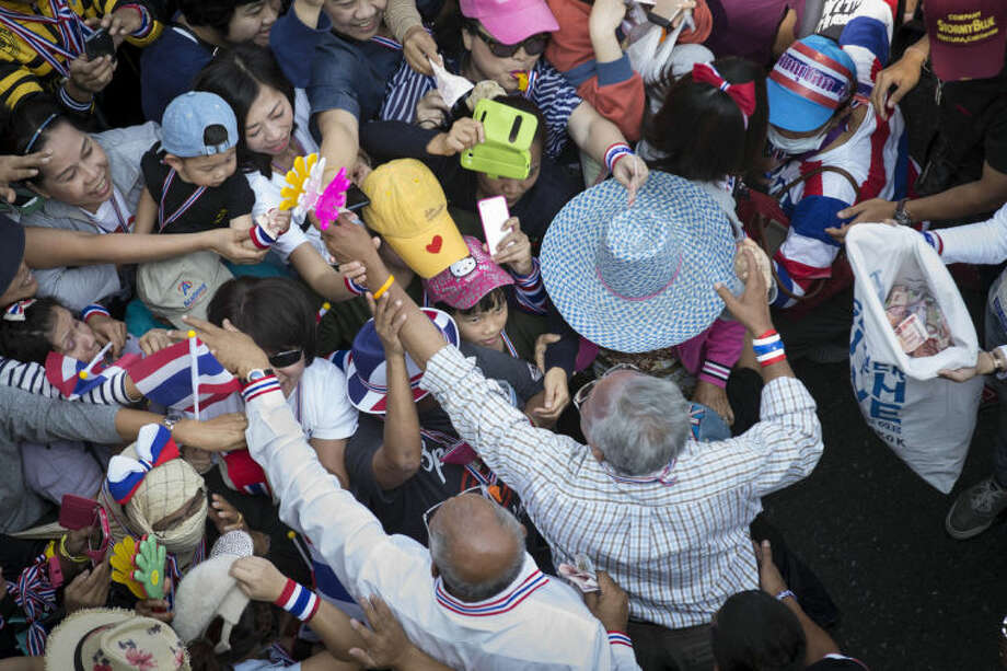A girl looks up at anti-government protest leader Suthep Thaugsuban, bottom right, as he greets supporters and collects donations, Sunday, Jan. 19, 2014, in Bangkok. Two explosions shook an anti-government demonstration site in Thailand's capital on Sunday, wounding at least 28 people in the latest violence to hit Bangkok as the nation's increasingly volatile political crisis drags on. (AP Photo/John Minchillo)