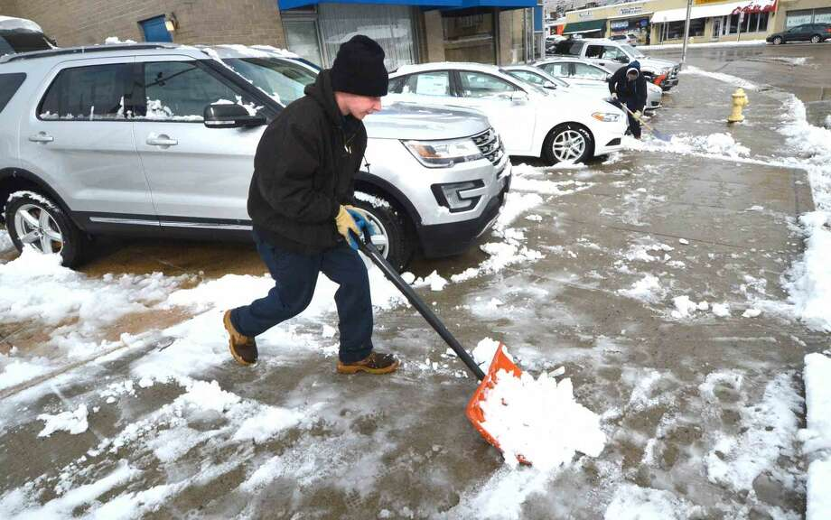 Hour Photo/Alex von Kleydorff Scott Bassett clears the snow from around some of the new cars at McMahon Ford, with over 100 cars new and used that need to be cleared of snow, moved, the lot plowed and then moved back takes some time.