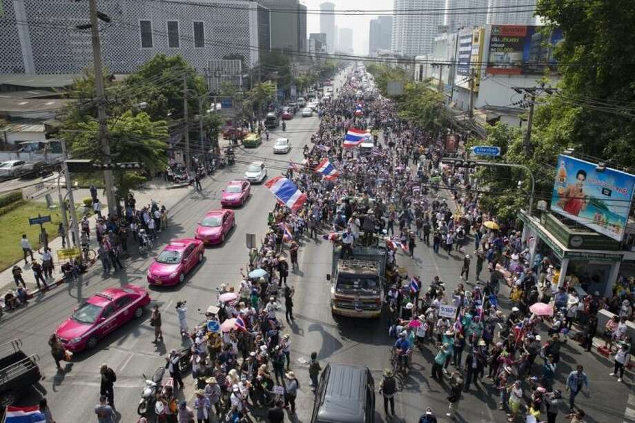Anti-government protesters block traffic during a march, Sunday, Jan. 19, 2014, in Bangkok. Two explosions shook an anti-government demonstration site in Thailand's capital on Sunday, wounding at least 28 people in the latest violence to hit Bangkok as the nation's increasingly volatile political crisis drags on. (AP Photo/John Minchillo)