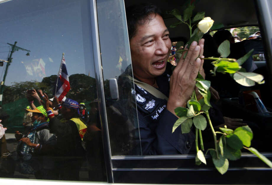 A Thai border policeman holds roses and greets back to anti-government protesters while leaving the prime minister's office of government house Sunday, Jan. 19, 2014 in Bangkok, Thailand. Police on Sunday withdrew a number of their unit out of the government house compound under the request of protesters. Two explosions shook an anti-government demonstration site in Thailand's capital on Sunday, wounding at least 28 people in the latest violence to hit Bangkok as the nation's increasingly volatile political crisis drags on. (AP Photo/Wason Wanichakorn)