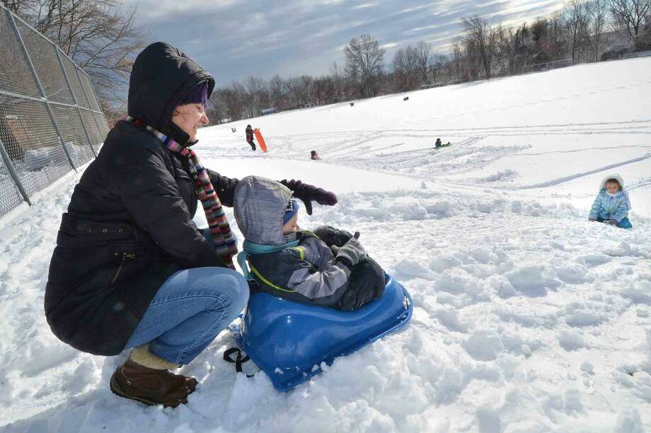 Hour Photo/Alex von Kleydorff Tatiana Tatarchevskiy loads 5yr old Artyom into his sled while his sister Katya waits at the bottom of the hill while sledding at West Rocks School