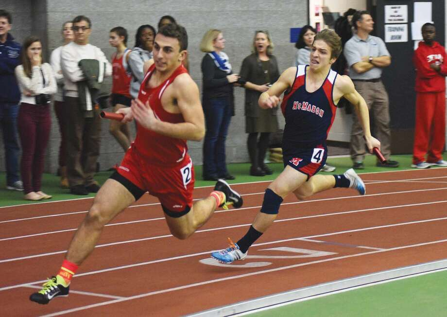 Hour photo/John Nash - Brien McMahon's Niko Petridis, right, chase down a Greenwich runner during the boys 4x200 relay at Thusday's FCIAC indoor track championship meet at the Floyd Little Athletic Center.