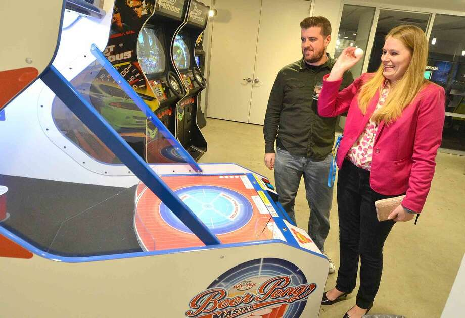 Hour Photo/Alex von Kleydorff Megan Rexroat and C.J. Barrett play a game of Beer Pong Master during a party to celebrate DATTO's new space connected by a grand staircase at 101 Merritt 7