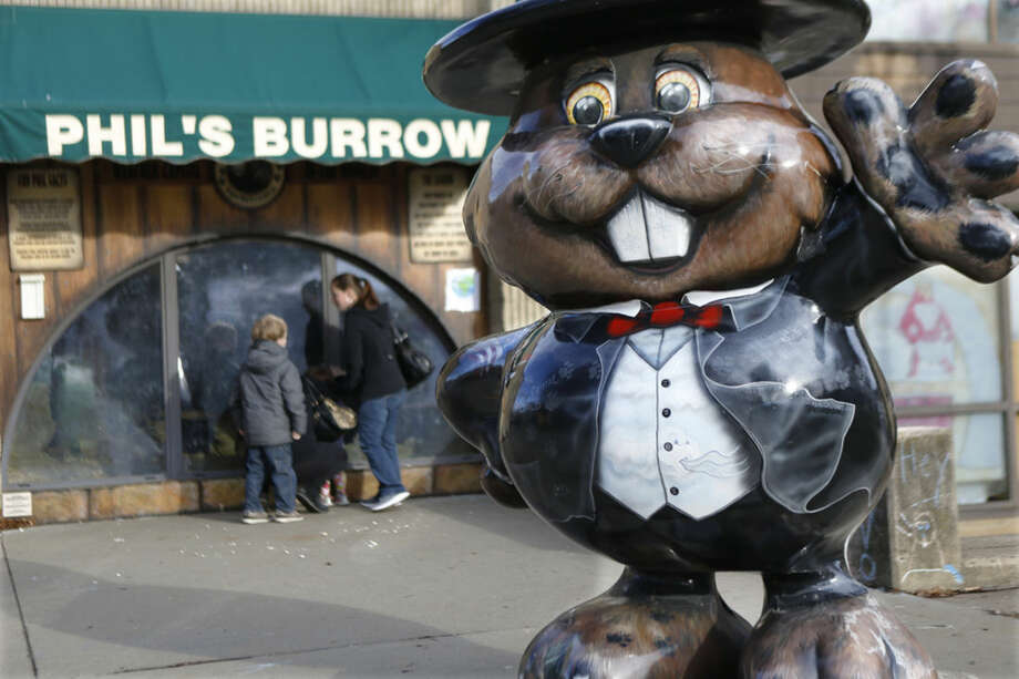 """Visitors look through the windows at the Punxsutawney Public Library where groundhogs are on display at """"Phil's Burrow"""" in Punxsutawney, Pa., Monday, Feb. 1, 2016. Thousands of people come to Punxsutawney for the annual celebration of Groundhog Day on Gobbler's Knob on Feb. 2. (AP Photo/Keith Srakocic)"""