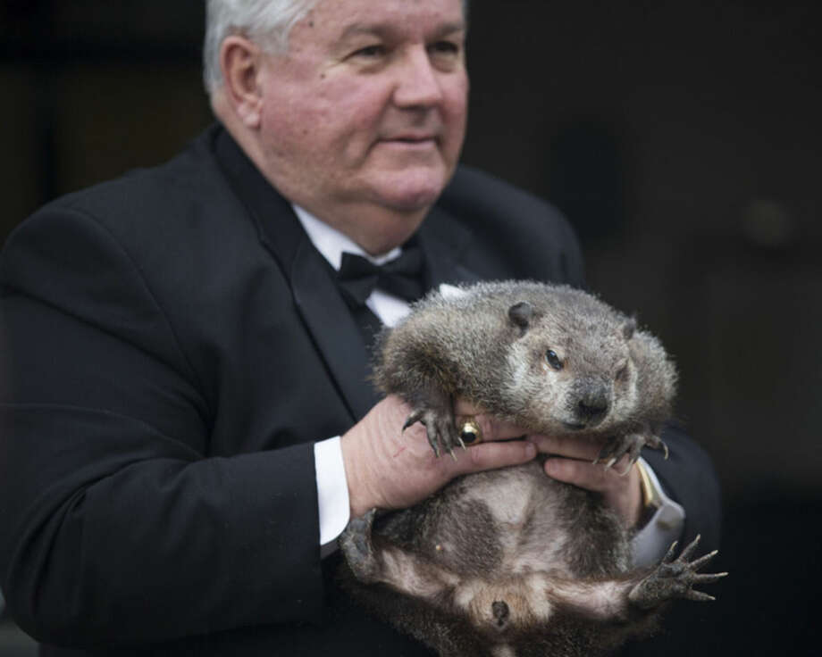 "Inner Circle President Bill Deeley shows Punxsutawney Phil to tourists a day before Groundhog Day in Punxsutawney, Pa., on Monday, Feb. 1, 2016. Members of the Inner Circle planned to reveal their forecast at sunrise Tuesday. A German legend says that if a furry rodent sees his shadow on Feb. 2, winter will last an additional six weeks. If not, spring comes early. In reality, Phil's ""prediction"" is decided ahead of time by the group. (Mark Pynes/PennLive.com via AP)"