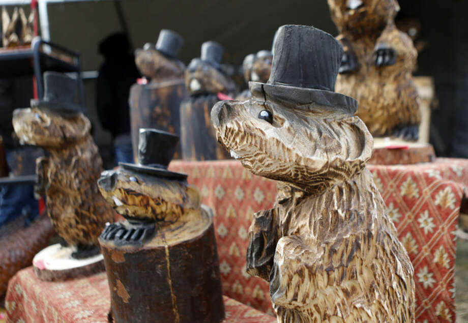 Wooden carvings of top hat wearing groundhogs are for sale at an annual craft show in the square in Punxsutawney, Pa., Monday, Feb. 1, 2016. That is part of the town's annual celebration of Groundhog Day on Feb. 2. (AP Photo/Keith Srakocic)