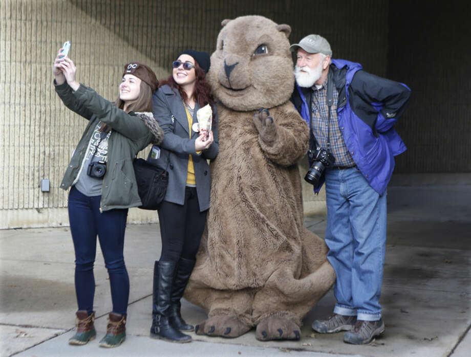 "A group of visitors pose for pictures and take selfies with the ""Punxsutawney Phil"" mascot outside the public library in Punxsutawney, Pa., Monday, Feb. 1, 2016. Thousands of people come to Punxsutawney for the annual celebration of Groundhog Day on Gobbler's Knob on Feb. 2. (AP Photo/Keith Srakocic)"