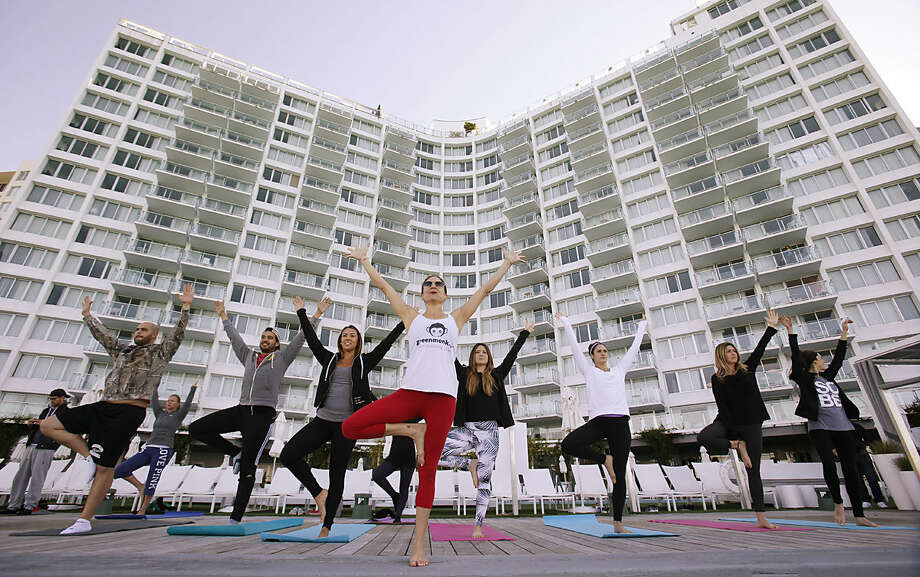 In this Jan. 24, 2016, photo, Paula Walker, center foreground, an instructor with Green Monkey Yoga, leads a yoga class at the Mondrian South Beach Hotel in Miami Beach, Fla. The hotel world is moving beyond basement gyms and ho-hum spa menus to accommodate guests' growing requests to stay healthy while on the road. (AP Photo/Wilfredo Lee)