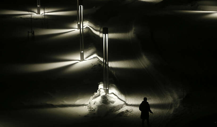 A pedestrian smokes a cigarette as she walks on a snow covered pathway in Alta, northern Norway, Monday, Feb. 1, 2016. (AP Photo/Alastair Grant)