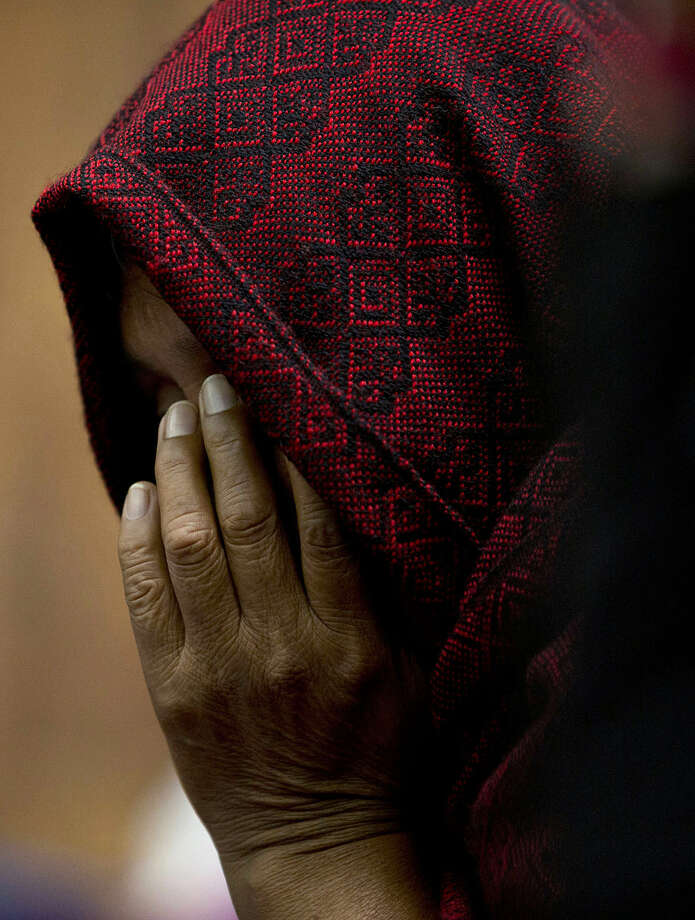 An indigenous woman wears a scarf to hide her face on the first day of hearings for a trial against a former military officer and former paramilitary fighter accused of sexual violence during Guatemala's civil war in Guatemala City, Monday, Feb. 1, 2016. Military forces are accused of subjecting indigenous Q'eqchi women to systematic sexual and domestic slavery in 1982 after repeatedly attacking Sepur Zarco, a small village in northern Guatemala, where community leaders were killed or disappeared. (AP Photo/Moises Castillo)