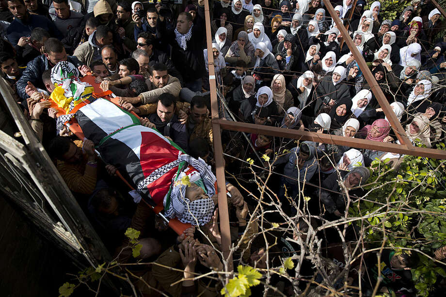 Palestinian mourners carry the body of Amjad Sukkari during his funeral in the village of Jammain near the West Bank city of Nablus, Monday, Feb. 1, 2016, who was shot and killed Sunday as he opened fire at a West Bank checkpoint and wounded three Israeli soldiers, the Israeli military said. (AP Photo/Majdi Mohammed)