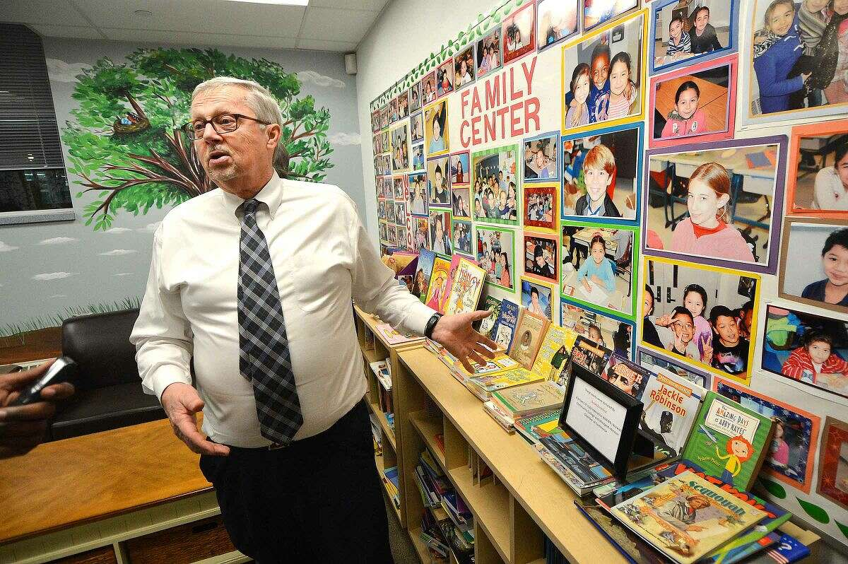 Hour Photo/Alex von Kleydorff Principal David Hay shows some of the boooks in the library area of the new Brookside School Family Resource Center