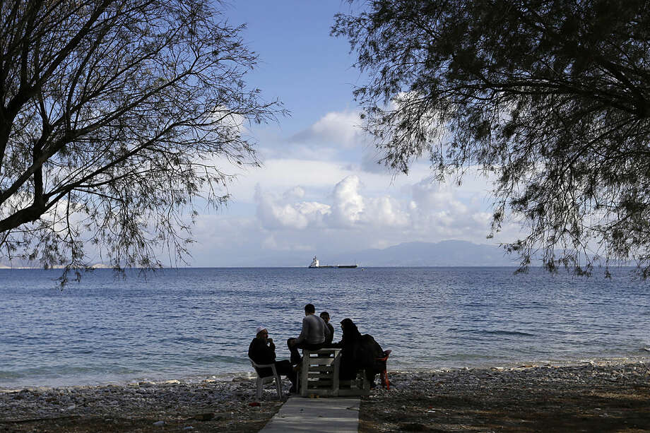 ? refugee family sits on the beach at Pothia port, on the southeastern Greek island of Kalymnos, Monday, Feb. 1, 2016. European countries have been strained by the influx of migrants, leading to disagreements over what to do with the large number of new arrivals and how to share the burden. (AP Photo/Thanassis Stavrakis)