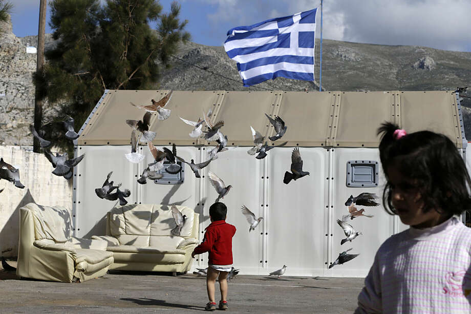 A child plays with the pigeons as a Greek flag waves at a small refugee camp at Pothia port, on the southeastern Greek island of Kalymnos, Monday, Feb. 1, 2016. European countries have been strained by the influx of migrants, leading to disagreements over what to do with the large number of new arrivals and how to share the burden. (AP Photo/Thanassis Stavrakis)