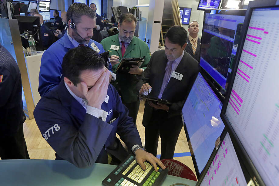 Specialist Michael Gagliano, foreground, works with traders at his post on the floor of the New York Stock Exchange, Monday, Feb. 1, 2016. Another steep drop in oil and natural gas prices is pulling the stock market lower in early trading. (AP Photo/Richard Drew)