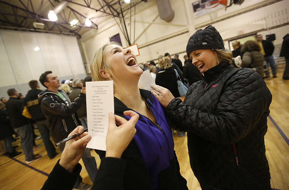 Kassidy Reis, center, serves as a writing surface for Kerri Reis, mother, and Rachel Reeg, friend, as they participate in a caucus at Eleanor Roosevelt Middle School, in Dubuque, Iowa, Monday, Feb. 1, 2016. (Mike Burley/Telegraph Herald via AP) MANDATORY CREDIT