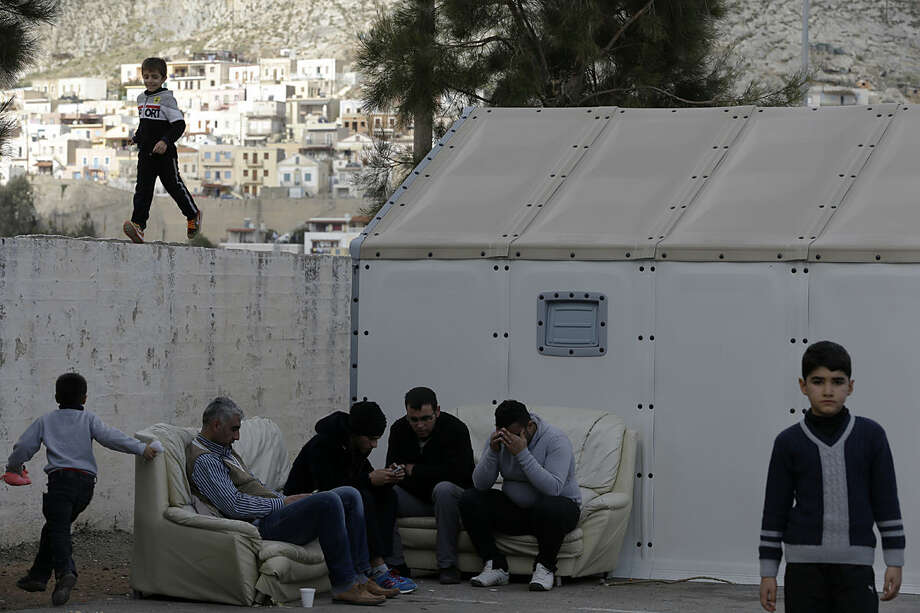 Refugees check their cell phones as a child runs atop of a cement wall at a small refugee camp at Pothia port, on the southeastern Greek island of Kalymnos, Monday, Feb. 1, 2016. European countries have been strained by the influx of migrants, leading to disagreements over what to do with the large number of new arrivals and how to share the burden. (AP Photo/Thanassis Stavrakis)