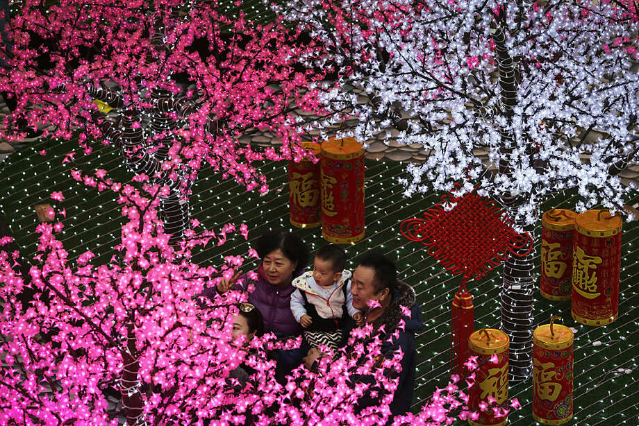 A Chinese family takes a selfie in front of trees decorated with light installations for the upcoming Chinese Lunar New Year at a shopping mall in Beijing, Monday, Feb. 1, 2016. Chinese will celebrate the Lunar New Year on Feb. 8 this year which marks the Year of Monkey on the Chinese zodiac. (AP Photo/Andy Wong)