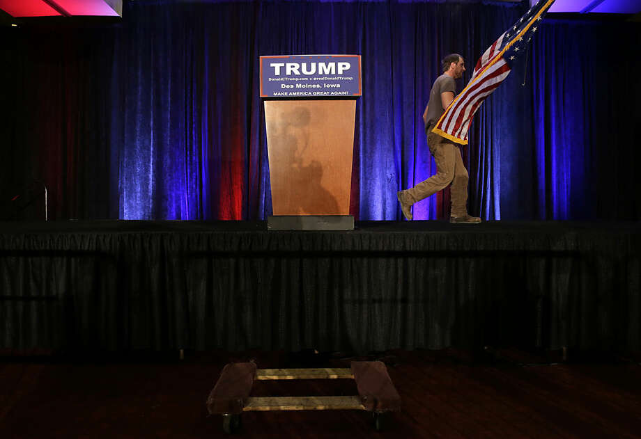 A worker walks off the stage as he takes the flag after Republican presidential candidate, businessman Donald Trump spoke at his caucus night rally, Monday, Feb. 1, 2016, in West Des Moines, Iowa. (AP Photo/Jae C. Hong)