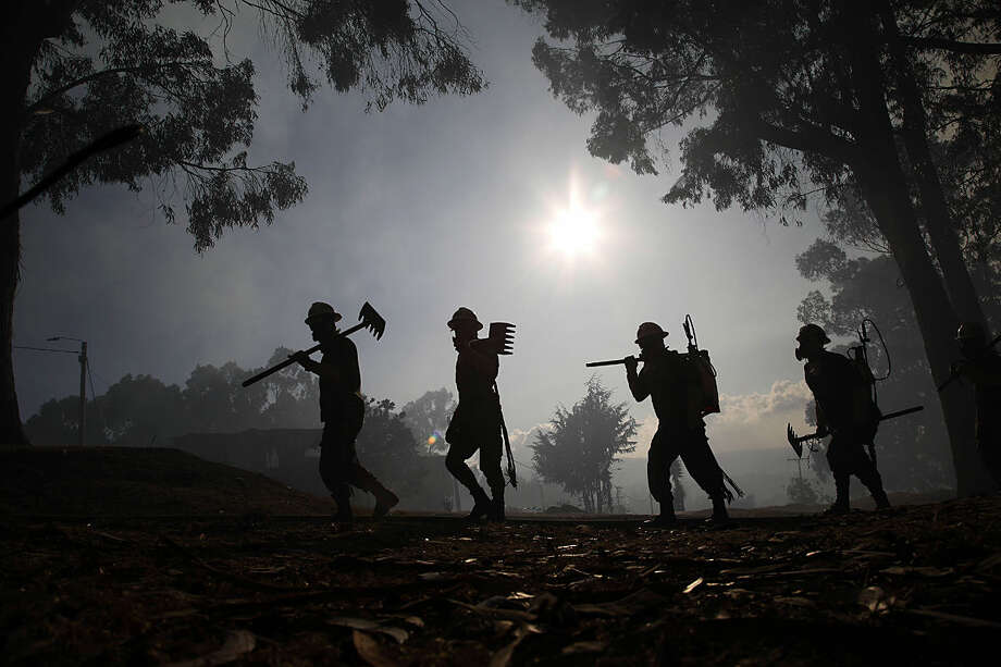 Soldiers arrive to help control a wildfire in a forest area on the mountains surrounding Bogota, Colombia, Monday, Feb. 1, 2016. Most of the country is under red alert because of water shortages and risk of wildfires. El Niño-related effects have intensified the regional dry season and there has been a record lack of rainfall this year. (AP Photo/Fernando Vergara)