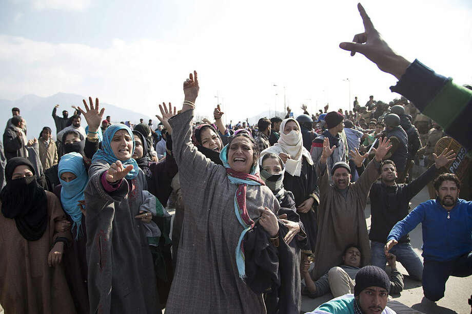 Kashmiri residents shout slogans against government as they block a road to stop authorities from pulling down illegally built structures around the Nigeen Lake in Srinagar, Indian controlled Kashmir, Monday, Feb. 1, 2016. Though police used tear gas and batons to disperse the residents, authorities returned without removing any of the illegally built structures Monday. (AP Photo/Dar Yasin)