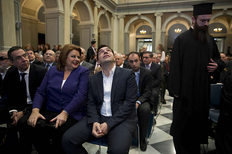 Greek Prime Minister Alexis Tsipras, center, looks up next to the Chair of the Board in National Bank of Greece Louka Katseli , second left, during a National Bank's event on presenting Act4Greece on Monday, Feb 1, 2016. Greece's leftwing-led government is entering a new round of negotiations with its creditors over progress on the latest bailout program, amid angry union reactions to proposed pension reforms _ a key part of the talks. (AP Photo/Petros Giannakouris)