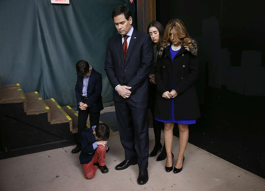 Republican presidential candidate Sen. Marco Rubio, R-Fla., and his family pray during opening of a caucus site, Monday, Feb. 1, 2016 in Clive, Iowa. (AP Photo/Paul Sancya)