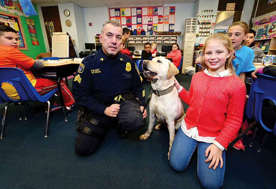 "Hour photo / Erik Trautmann Marvin Elementary School 5th grader, Victoria Bumberova, meets with Norwalk police sergeant Frank Reda, Supervisor of the Police Department's K-9 division, and their new bomb-sniffing dog, a Labrador Retreiver, she named ""Rocco"" after winning a district-wide contest sponsored by the Department."