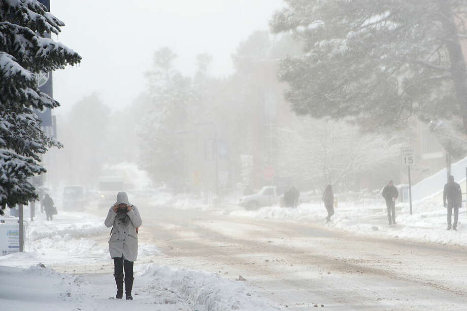 Students on the campus of Northern Arizona University navigate through blustery weather in Flagstaff, Ariz., Monday, Feb. 1, 2016. A winter storm dropped snow on the region, closing schools and making travel difficult. (AP Photo/Josh Biggs)
