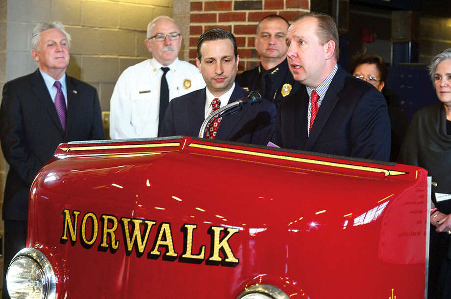 Hour photo / Erik Trautmann Mike Chowaniec, Area Director of Governmental Affairs for Cablevision, speaks as State Senate Majority Leader Bob Duff joins Norwalk Mayor Harry Rilling, to present checks to Norwalk nonprofits as part of a Duff's holiday giving campaign Friday morning at the Norwalk Fire Department Headquarters. Senator Duff helped coordinate the donation of $16,500 by businesses including Altria, Aetna, Cablevision, Dominion, The Travelers, and others, to Norwalk Reads!, Norwalk PAL, The Children's Connection,The Carver Foundation, Person-to-Person, St. Vincent De Paul, and Community Plates during the brief ceremony.