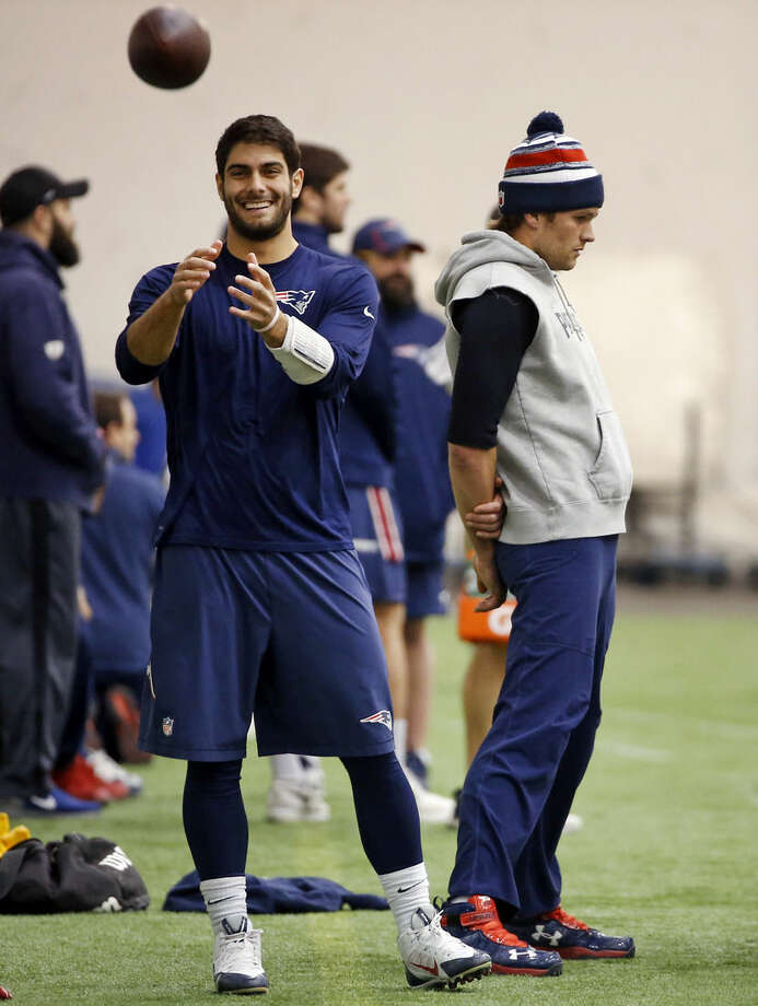 New England Patriots backup quarterback Jimmy Garoppolo, left, catches a football as starting quarterback Tom Brady, right, stands by during a walkthrough at the NFL football team's facility in Foxborough, Mass., Friday, Jan. 23, 2015. The Patriots face the Seattle Seahawks in Super Bowl XLIX on Sunday, Feb. 1, 2015, in Glendale, Ariz. (AP Photo/Elise Amendola)