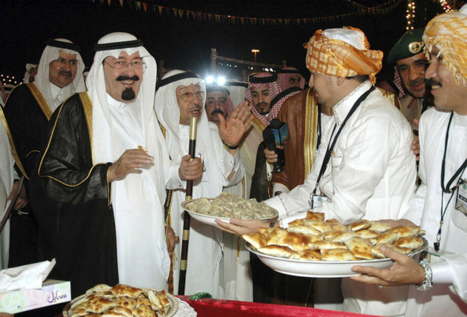 FILE - In this file photo taken Saturday, Nov. 12, 2005, Saudi King Abdullah, second left, eats popular staple food at a park in Mecca, Saudi Arabia. On early Friday, Jan. 23, 2015, Saudi state TV reported King Abdullah died at the age of 90. (AP Photo/Khaled Mahmoud, File)