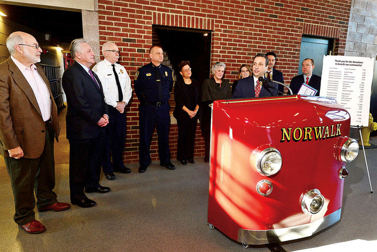 Hour photo / Erik Trautmann State Senate Majority Leader Bob Duff joins local business representative Mike Chowaniec, Area Director of Governmental Affairs for Cablevision, far right, and Norwalk Mayor Harry Rilling, second from left, to present checks to Norwalk nonprofits as part of a Duff's holiday giving campaign Friday morning at the Norwalk Fire Department Headquarters. Senator Duff helped coordinate the donation of $16,500 by businesses including Altria, Aetna, Cablevision, Dominion, The Travelers, and others, to representatives including; Executive Director Stephen Bentkover for Norwalk Reads!, Norwalk Fire Chief Denis McCarthy for the Fire Victims Fund, Norwalk Police Chief Thomas Kulhawik for Norwalk PAL, Executive Administrator Elsie Lopez for the Carver Foundation, Executive Director Cici Maher for Person-to-Person, Executive Director Kari Pesavento for the Children's Connection, and Executive Director Kevin Mullins for Community Plates during the brief ceremony.