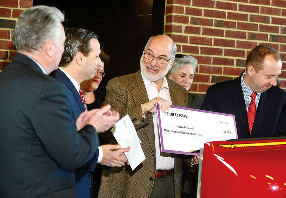 Hour photo / Erik Trautmann Executive Director for Norwalk Reads!, Stephen Bentkover, receives a check from State Senate Majority Leader Bob Duff for $1500 as the sennator presents checks to Norwalk nonprofits as part of a Duff's holiday giving campaign Friday morning at the Norwalk Fire Department Headquarters. Senator Duff helped coordinate the donation of $16,500 by businesses including Altria, Aetna, Cablevision, Dominion, The Travelers, and others, to Norwalk Reads!, Norwalk PAL, The Children's Connection,The Carver Foundation, Person-to-Person, St. Vincent De Paul, and Community Plates during the brief ceremony.