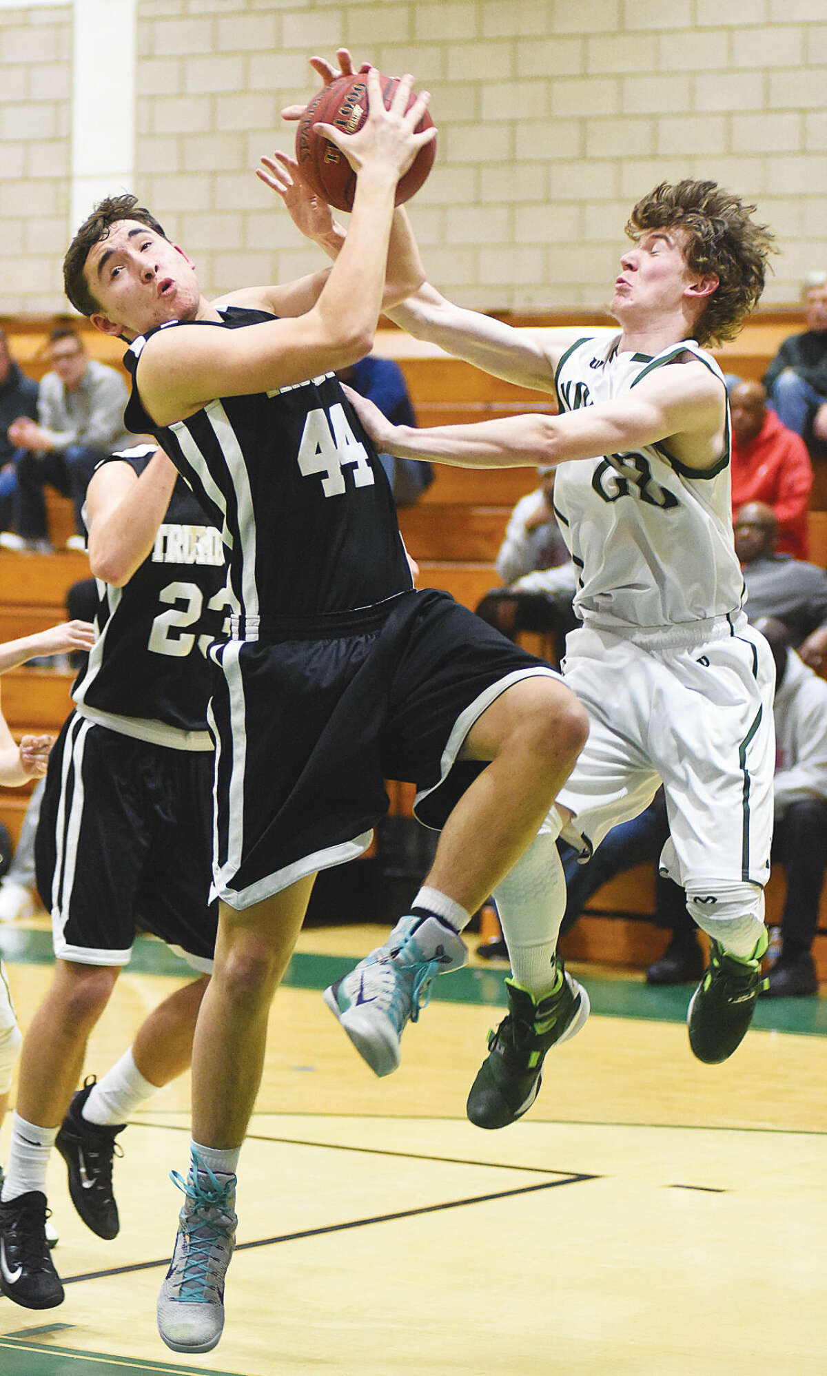 Hour photo/John Nash - Norwalk's Ryan Searles, right, scraps with Trumbull's Alex Recker during the second half of Monday's FCIAC boys basketball game in Norwalk.
