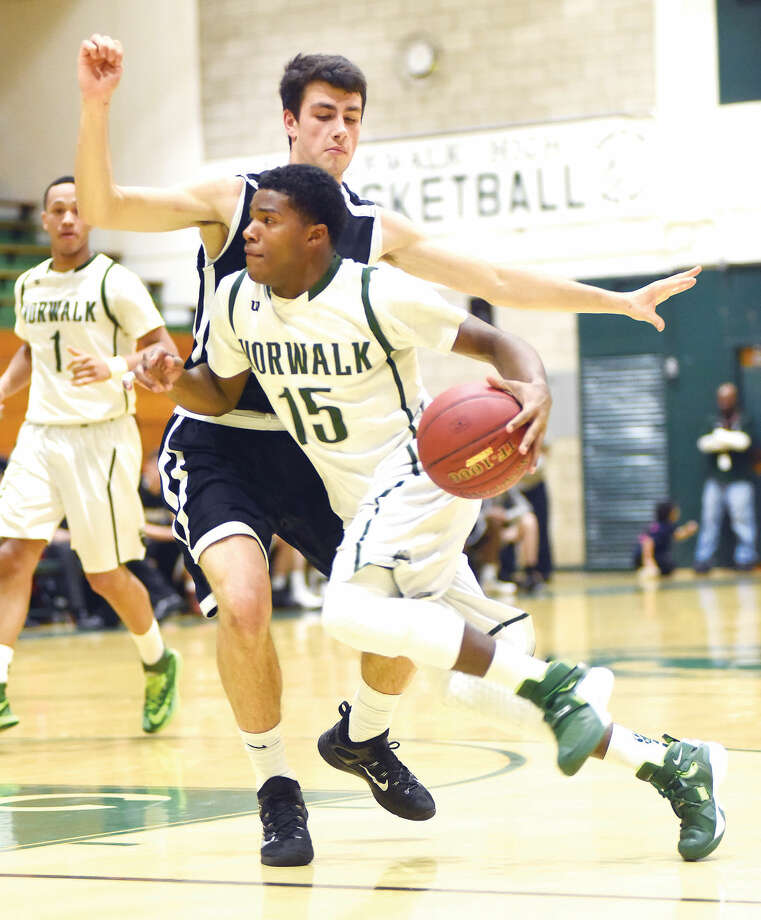 Hour photo/John Nash Norwalk's Tyrique Langley (15) drives past a Trumbull defender during the second half of Monday's FCIAC boys basketball game at Scarso Gym in Norwalk. The Bears led at the break, but only scored nine points in the second half and fell 68-40 to the Eagles.