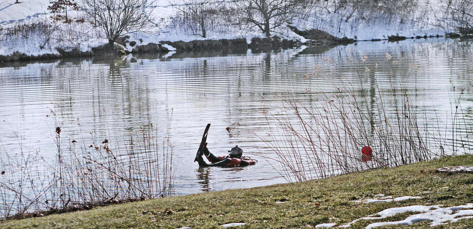 In this Jan. 31, 2016 photo, trooper Christopher Grzelak puts on his flippers as he gets ready to dive into the Duck Pond, in Blacksburg, Va. The investigation continued in the death of Nicole Madison Lovell as a state police search and recovery team searched the pond for evidence on the Virginia Tech Campus. (Edmee Rodriguez/The Roanoke Times via AP) LOCAL TELEVISION OUT; SALEM TIMES REGISTER OUT; FINCASTLE HERALD OUT; CHRISTIANBURG NEWS MESSENGER OUT; RADFORD NEWS JOURNAL OUT; ROANOKE STAR SENTINEL OUT; MANDATORY CREDIT