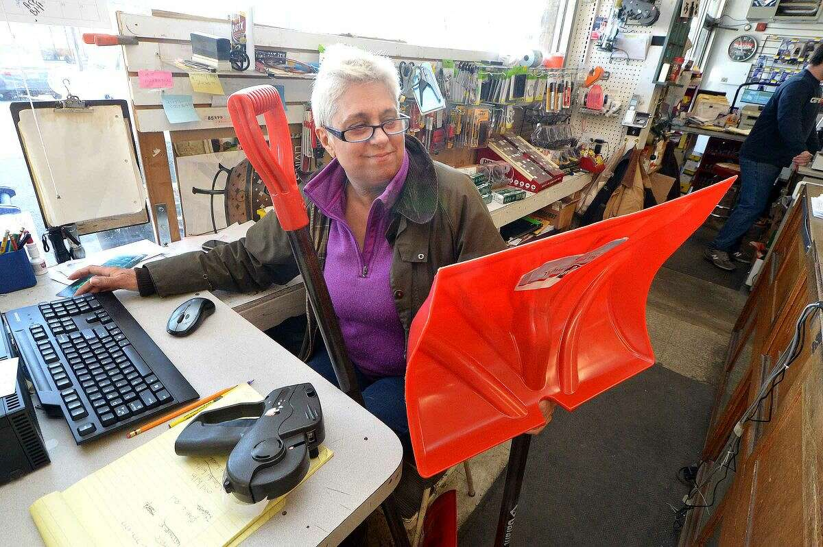 Hour Photo/Alex von Kleydorff At Carlyn Hardware Deborah Hayden rings up some snow shovels on Friday as residents prepare for a winter storm to hit the area